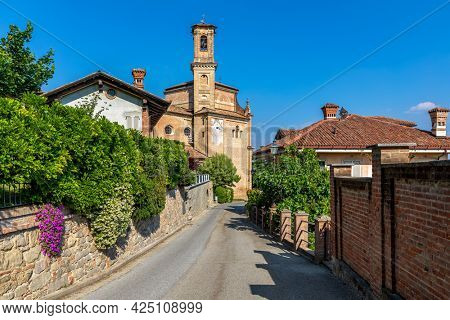 Narrow street, houses with green bushes and old brick church under blue sky in small town of Guarene in Piedmont, Northern Italy.
