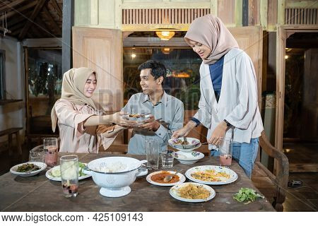 A Veiled Woman Gives Some Dirty Plates To A Man After Breaking The Fast Together