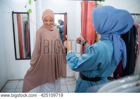A Beautiful Girl In A Veil Trying On Clothes In A Changing Room In Front Of The Mirror And Her Frien