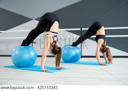 Two Strong Fit Women Training Abdominal Muscles, Using Big Blue Fitness Balls In Ballet Studio. Gorg
