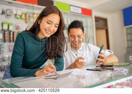 A Beautiful Woman Shop Assistant Using A Calculator