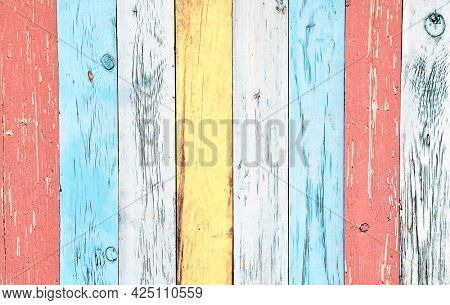 Texture of vintage wood boards with cracked paint of white, red, yellow and blue color. Horizontal retro background with old wooden planks