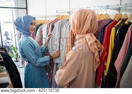 A Female Customer In A Veil Chooses Clothes When A Waiter Serves Her When Choosing Clothes On A Hang