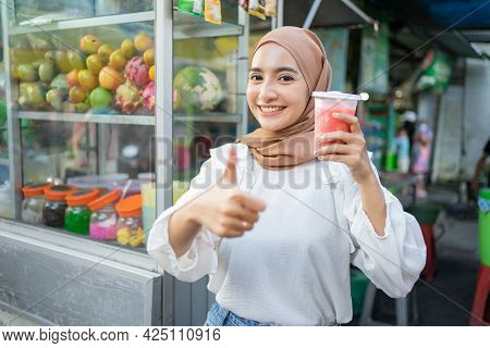 Beautiful Girl In Hijab Smiles At The Camera With Thumbs Up While Holding A Plastic Cup Of Fruit Jui