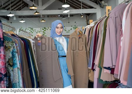 A Woman In The Veil Of A Shop Assistant Holding Two Robes To Show While Standing