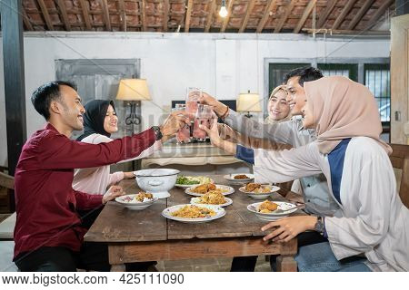 Group Of Friends Celebrate And Raise Glasses Of Fruit Ice For Toast When Breaking Fast Together
