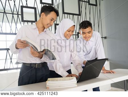 Three Teenagers Study Together In School Uniforms Using A Laptop And Several Books