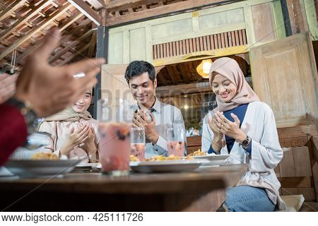 Group Of Young Asian People Praying Together Before Breaking Fast