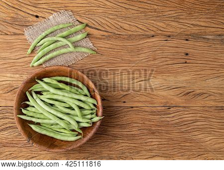 A Group Of Green Bean Pods In A Bowl Over Wooden Table With Copy Space.