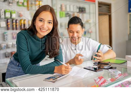 Beautiful Woman Shop Assistant Smiling While Working With A Man Checking Goods Note Paper With Notes