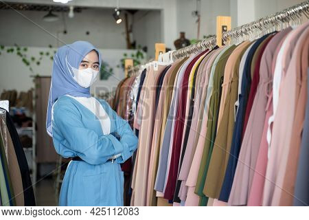 A Girl In A Headscarf Wearing A Mask In Blue And Crossing Her Arms Is Standing