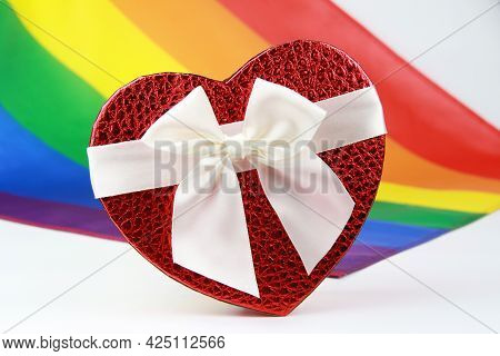 Red Gift Box In The Shape Of A Heart On The Background Of A Rainbow Lgbt Flag.the Design Concept Of