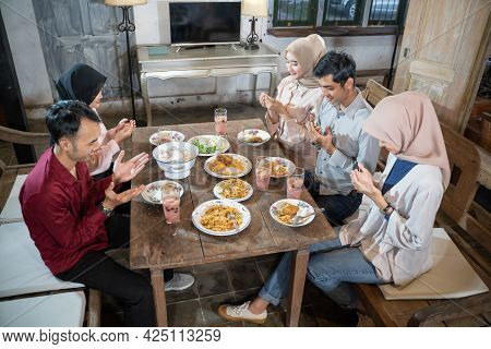 Two Muslim Men And Three Veiled Women Pray Together Before Eating