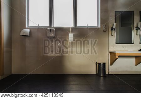 Bathroom Interior With Air Hand Dryer, Paper Towel Holder, Luminous Lamps. There Is A Mirror Reflect
