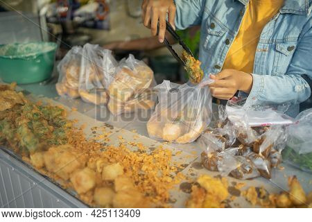 The Seller Uses Tong Tongs To Take The Fried Food Into A Plastic Wrapper