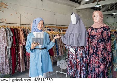 A Veiled Woman A Tablet While Holding A Headscarf Mannequin
