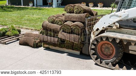 A Compact Front End Loader And A Pallet With Rolls Of Fresh Sod Grass For Installation At A New Home