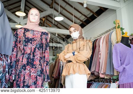 Asian Woman In A Hijab Wearing A Mask And Crossing Hands Stands