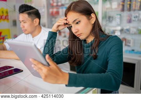 A Sad Businesswoman Facing Some Problems While Using A Tablet Beside A Man