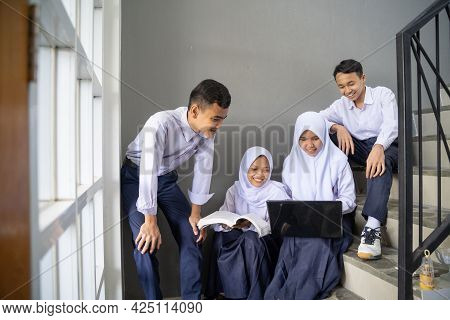 A Group Of Asian Teenagers In Junior High School Uniforms Study Together Using A Laptop And A Book
