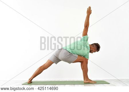 Back View Of Sporty Man Practicing Yoga In Yoga Class, Making Stretching Back. Healthy Lifestyle, Yo