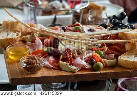 Assorted Cheeses In Various Shapes And Sizes And Honey