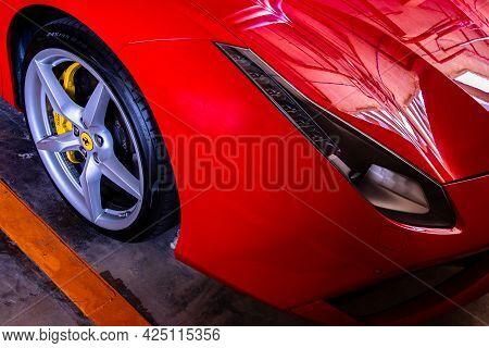 Bangkok, Thailand - 06 Jun 2021 : Close-up Of Headlights, Wheel, And Rim Of Red Metallic Ferrari Car