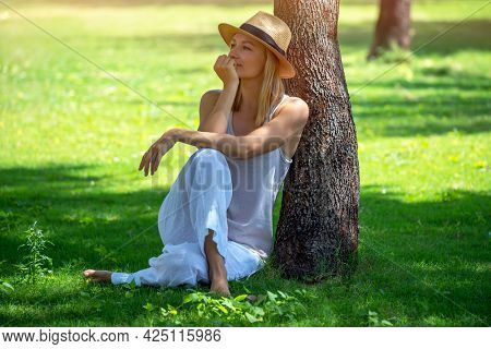 Pretty Woman in the Park. Nice Calm Female Sitting on the Ground near Tree Trunk on Sunny Green Grass Glade. Enjoying Mild Spring Summer Weather.
