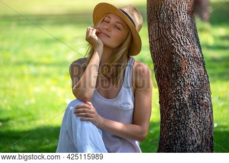 Portrait of a Pretty Woman with Closed Eyes of Pleasure Wearing Stylish Sun Hat in the Park. Resting Near the Tree on Fresh Green Grass. Enjoy Summer.