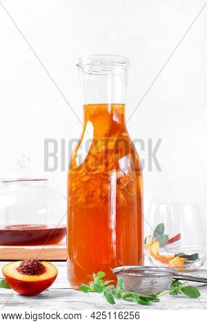 Bottle Of Iced Tea With Nectarine, Peach And Lemon On The White Table. Making Refreshing Summer Drin