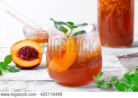 Iced Tea With Nectarines Topped With Mint In Drinking Glass On The White Table. Refreshing Summer Dr