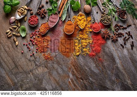 Various Colorful Herbs And Spices In Spoons For Cooking: Turmeric, Dill, Paprika, Cinnamon, Saffron,