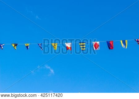 Maritime Flags Against Blue Sky. Nautical Flags Fluttering In The Wind. Colorful Signal Flags