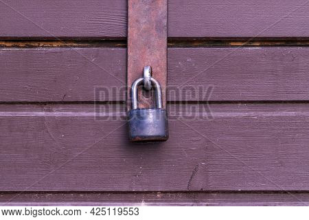 Black Padlock On The Door Of A Wooden Stand. Locked Window With A Padlock.