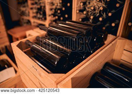 Dusty Bottles Of Wine In Storage Room Or Wine Cellar