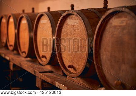 Wooden Wine Barrels On Shelf In Wine Cellar