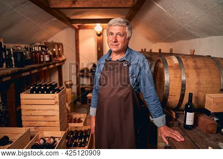 Handsome Man In Apron Standing In Wine Cellar