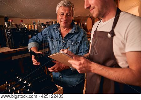 Two Men Working Together In Winery Cellar