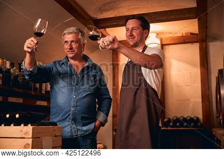 Smiling Male Caucasians Looking At The Color Of Wine In Cellar