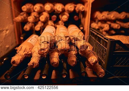 Bottles Of Wine Packed In Craft Paper In The Cellar