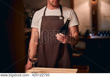 Skilled Young Sommelier Choosing Wine In Cellar