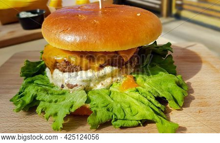 Freshly Made Grilled Hamburger With Fresh Salad Leaves And Mustard Sauce - Ready To Eat. Enjoy Your