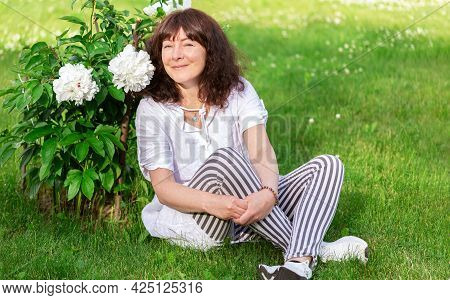 Portrait Of  Beautiful Woman Of Forty-five Years Old With Brown Hair, Sitting On Green Lawn In Sun A