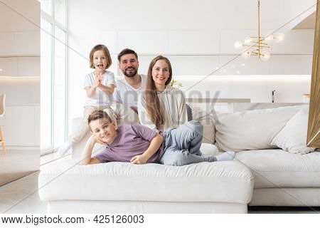 Family Portrait Of Young Parents With Their Two Children At Home, White Modern Desgin Of Living Room