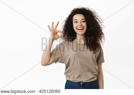 All Under Control. Smiling Young Woman Assure Everything Ok, Showing Okay Sign And Say Yes, Approve