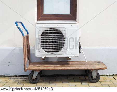 The Air Conditioner Hangs On The Wall Of The Building Outside Above The Pushcart Standing On The Til