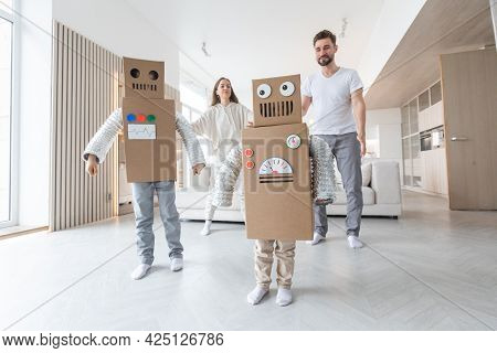 Happy Family Of Parents And Two Children Playing Dancing Like Robots At Home, Children Wearing Handm