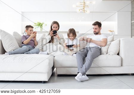 Caucasian Parents And Kids Use Devices Together Sit On Sofa, Tech Addicted Family With Children Hold
