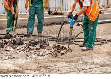 Road Workers In Green Overalls Repair An Old Stretch Of Road By Loosening Old Asphalt With A Pneumat