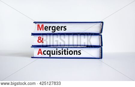 Mergers And Acquisitions Symbol. Concept Words 'm And A, Mergers And Acquisitions' On Books On A Bea